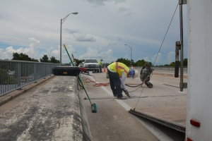 Crews work to clean and install new deck joints on the US 41 bridge in Lake City.